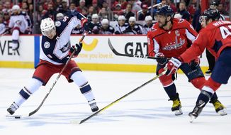 Columbus Blue Jackets left wing Artemi Panarin (9), of Russia, skates with the puck against Washington Capitals left wing Alex Ovechkin (8), of Russia, and right wing Tom Wilson (43) during the first period in Game 2 of an NHL first-round hockey playoff series, Sunday, April 15, 2018, in Washington. (AP Photo/Nick Wass)