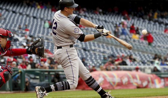 Colorado Rockies' DJ LeMahieu hits a home run during the eighth inning of a baseball game against the Washington Nationals at Nationals Park, Sunday, April 15, 2018, in Washington. (AP Photo/Andrew Harnik)