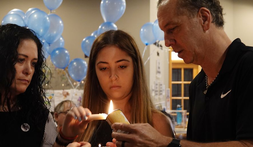 Marjory Stoneman Douglas High School student Samantha Mayor lights a candle during the Yom HaShoah candle lighting ceremony, Sunday, April 15, 2018, at the Downtown Jewish Center Chabad Education Center, in Fort Lauderdale as her parents Ellyn and Jesse help. The ceremony remembers victims of the holocaust and she also lit 17 candles for the victims of the Parkland school shooting. (Joe Cavaretta/South Florida Sun-Sentinel via AP)