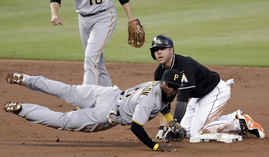 Miami Marlins' JB Shuck, right, is out at second as Pittsburgh Pirates second baseman Josh Harrison (5) throws to first during the second inning of a baseball game, Saturday, April 14, 2018, in Miami. Lewis Brinson was out at first on a fielder's choice. (AP Photo/Lynne Sladky)