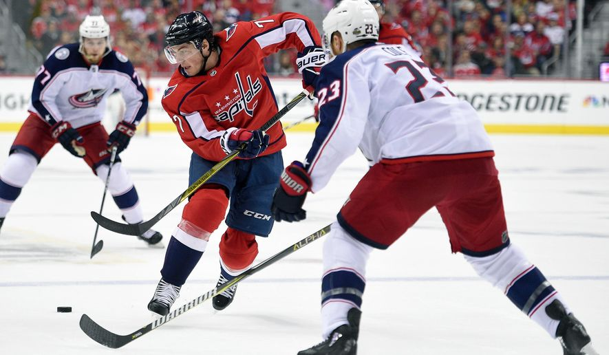 Washington Capitals right wing T.J. Oshie (77) chases the puck against Columbus Blue Jackets defenseman Ian Cole (23) during the second period in Game 2 of an NHL first-round hockey playoff series, Sunday, April 15, 2018, in Washington. (AP Photo/Nick Wass)