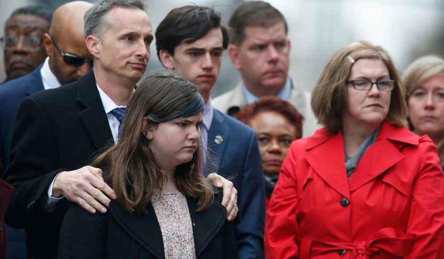 The family of Martin Richard, foreground from left, Bill, Jane, Henry and Denise, observe a moment of silence during a ceremony at the site where Martin Richard and Lingzi Lu were killed in the second explosion at the 2013 Boston Marathon, Sunday, April 15, 2018, in Boston. (AP Photo/Michael Dwyer)
