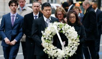 The father of Lingzi Lu, Jun Lu, foreground left, and her aunt Helen Zhao, foreground right, carry a wreath ahead of the family of Martin Richard, background from left, Henry, Bill, Denise and Jane, partially hidden, during a ceremony at the site where Martin Richard and Lingzi Lu were killed in the second explosion at the 2013 Boston Marathon, Sunday, April 15, 2018, in Boston. (AP Photo/Michael Dwyer)