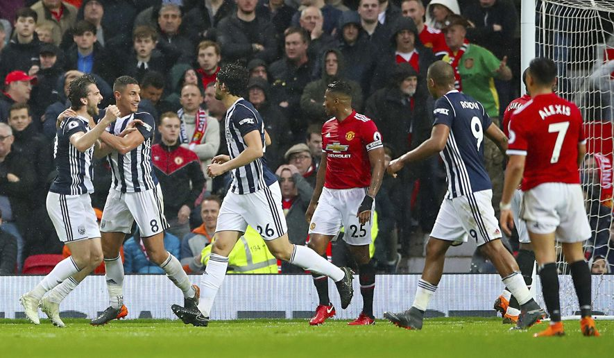 West Bromwich Albion's Jay Rodriguez, left, celebrates scoring his side's first goal of the game against Manchester United during the English Premier League soccer match at Old Trafford, Manchester, England, Sunday April 15, 2018. (Nick Potts/PA via AP)