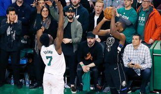 Milwaukee Bucks' Khris Middleton shoots a three-point basket over Boston Celtics' Jaylen Brown (7) with less than a second to play in the fourth quarter of Game 1 of an NBA basketball first-round playoff series in Boston, Sunday, April 15, 2018. The Celtics won 113-107 in overtime. (AP Photo/Michael Dwyer)