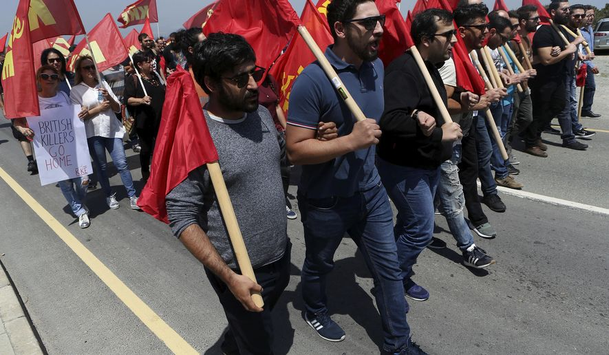 Protestors from the Greek communist party KKE, march during a protest against the airstrikes in Syria, at the Akrotiri Royal air forces near south coastal city of Limassol, Cyprus, Sunday, April 15, 2018. Hundreds protesters from communist organizations in Cyprus have gathered in front of the entrance gate of a British air base to denounce US-led airstrikes against suspected chemical weapons sites in Syria. (AP Photo/Petros Karadjias)