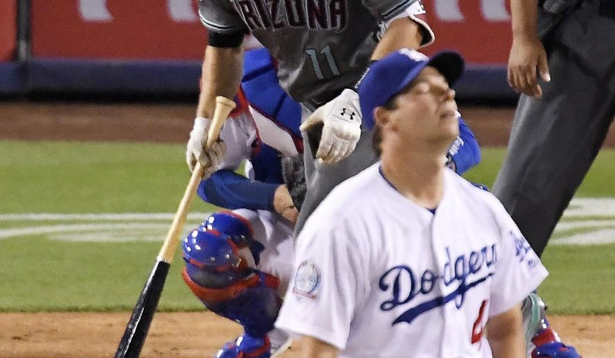 Arizona Diamondbacks' A.J. Pollock watches his two-run home run off Los Angeles Dodgers starting pitcher Rich Hill, foreground, during the fifth inning of a baseball game Saturday, April 14, 2018, in Los Angeles. (AP Photo/Mark J. Terrill)
