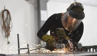 In this March 22, 2018 photo, welder Morgan Bledsoe uses a grinder to cut down metal pieces to size at the TEKFAB facility in Albany, Ore. (Amanda Loman/Albany Democrat-Herald via AP)