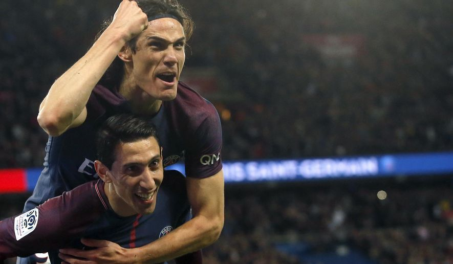 PSG's Angel Di Maria, down, celebrates with Edinson Cavani after scoring his side's third goal during the French League One soccer match between Paris Saint Germain and Monaco at the Parc des Princes stadium in Paris, Sunday, April 15, 2018. (AP Photo/Michel Euler)