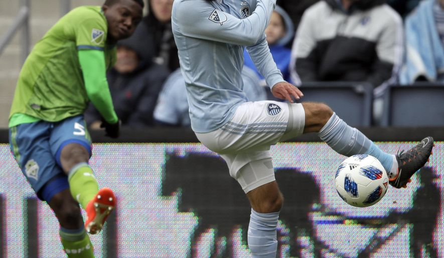 Sporting Kansas City midfielder Graham Zusi, right, blocks a kick by Seattle Sounders defender Nouhou Tolo (5) during the first half of an MLS soccer match in Kansas City, Kan., Sunday, April 15, 2018. (AP Photo/Orlin Wagner)