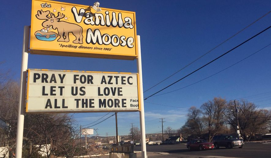FILE - In this Dec. 8, 2017, file photo, a sign encourages prayer outside an ice cream shop in Aztec, N.M., following a shooting at Aztec High School in which two classmates were killed before the gunman killed himself. Residents of the rural New Mexico town have worked hard to define a new normal following the December school shooting. But they say the healing process is far from over. (AP Photo/Russell Contreras, File)