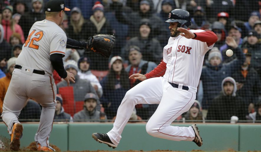 Boston Red Sox's J.D. Martinez, right, scores on a wild pitch by Baltimore Orioles' Dylan Bundy, left, in the sixth inning of a baseball game Sunday, April 15, 2018, in Boston. (AP Photo/Steven Senne)