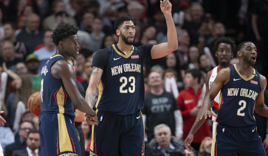 New Orleans Pelicans guard Jrue Holiday, forward Anthony Davis and guard Ian Clark celebrate a score against the Portland Trail Blazers during the second half in Game 1 of an NBA basketball first-round playoff series Saturday, April 14, 2018, in Portland, Ore. New Orleans won 97-95. (AP Photo/Randy L. Rasmussen)