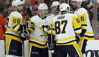 Pittsburgh Penguins' Sidney Crosby celebrates his goal with teammates during the first period in Game 3 of an NHL first-round hockey playoff series against the Philadelphia Flyers, Sunday, April 15, 2018, in Philadelphia, Pa. (AP Photo/Tom Mihalek)