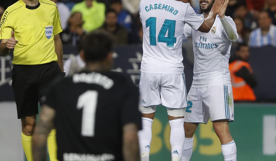 Real Madrid's Casemiro, second right, celebrates with teammate Isco, right, after scoring during La Liga soccer match between Real Madrid and Malaga at the Rosaleda stadium, in Malaga, Spain on Sunday, April. 15, 2018. (AP Photo/Miguel Morenatti)