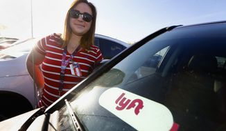 """In this Wednesday, April 11, 2018, photo, Stefanie Lowe, a teacher at Tuscano Elementary School, stands next to her car in the parking lot after joining other teachers, parents and students as they stage a """"walk-in"""" for higher pay and school funding in Phoenix. To help make ends meet Lowe is a Lyft driver in order to supplement her teaching salary in Arizona, where teachers are paid some of the lowest wages in the country. (AP Photo/Ross D. Franklin)"""