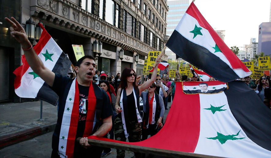 Syrian-Americans express their anger at the missile strikes on their homeland during an anti-war rally opposing the military strikes by Western countries in Syria, in downtown Los Angeles, Saturday, April 14, 2018. On Saturday, those commemorating Syria's independence from France in 1946, called the missile strikes by the U.S., Britain and France illegal. (AP Photo/Damian Dovarganes)