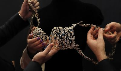 Workers put on a $2 million Champagne Nights Fantasy Bra which will modeled by Angel Lais Ribeiro at backstage before the Victoria's Secret fashion show inside the Mercedes-Benz Arena in Shanghai, China, Monday, Nov. 20, 2017. The Victoria's Secret fashion show takes place in Shanghai on Monday with performances from Singer Harry Styles and R&B star Miguel. (AP Photo/Andy Wong)