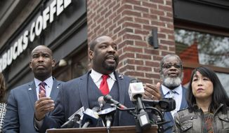 Philadelphia City Councilman, Kenyatta Johnson, center, flanked by two fellow members, speaks at the podium during a press conference outside the Starbucks on 18th and Spruce streets in Philadelphia, Monday, April 16, 2018. Two black men were arrested last week in a video incident that went viral over the weekend. (Jose F. Moreno/The Philadelphia Inquirer via AP)