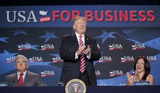 President Donald Trump, center, takes his seat before speaking at an event to promote his tax cut package at Bucky Dent Park in Hialeah, Fla., Monday, April 16, 2018. Siting with Trump are Maximo Alvarez, left, CEO, Sunshine Distributor and Irina Vilarino, right, owner, Las Vegas Cuban Cuisine. (AP Photo/Pablo Martinez Monsivais)