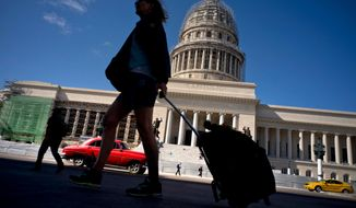 FILE - In this Jan. 18, 2018 file photo, a tourist walks with her suitcase in front of the Capitolio in Havana, Cuba. President Donald Trump drew cheers from a Cuban-American crowd last summer when he announced that he was rolling back some of Barack Obama's opening to Cuba in order to starve the island's military-run economy of U.S. tourism dollars and ratchet up pressure for regime change. (AP Photo/Ramon Espinosa, File)
