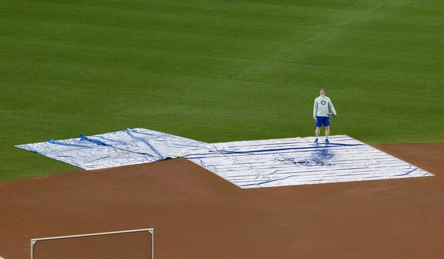 Toronto Blue Jays coach Tim Leiper looks up from tarps protecting the field at Rogers Centre from water coming through the roof in Toronto on Monday April 16, 2018. The Blue Jays baseball game against the Kansas City Royals was cancelled over safety concerns when ice falling from the CN Tower punched a hole in the roof. (Fred Thornhill/The Canadian Press via AP)
