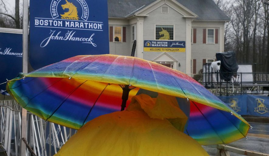 Cherry Scanzaroli, of Hopedale, Mass., holds a rainbow umbrella as she waits to cheer on runners at the start of the 122nd running of the Boston Marathon in Hopkinton, Mass., Monday, April 16, 2018. (AP Photo/Mary Schwalm)