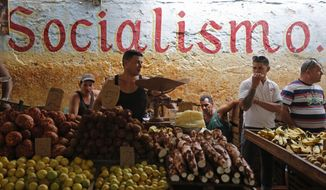 FILE - In this Dec. 20, 2014 file photo, workers stand behind their food stalls at a state-run market in Havana, Cuba. The average monthly state salary of $31 is so low that some workers often live on stolen goods and handouts from relatives overseas. (AP Photo/Desmond Boylan, File)