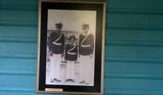 FILE - This June 10, 2016 file photo shows a family photograph of the Castro brothers, from left, Fidel, Raul and Ramon, on the wall of the room they shared as children in Biran, Cuba. Biran is the birthplace of revolutionary leader Fidel Castro and his brother, President Raul Castro. Their father Angel planted and sold sugarcane and timber as well as raising cattle deep in the lush green hill country of Holguin province in eastern Cuba. (AP Photo/Ramon Espinosa, File)