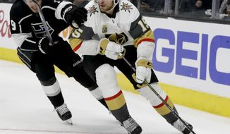 Los Angeles Kings left wing Adrian Kempe, left, battles Vegas Golden Knights defenseman Jon Merrill for the puck during the second period of Game 3 of an NHL hockey first-round playoff series in Los Angeles, Sunday, April 15, 2018. (AP Photo/Chris Carlson)