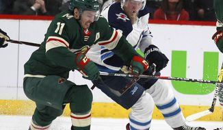 Minnesota Wild left wing Zach Parise (11) battles with Winnipeg Jets right wing Patrik Laine (29) in the first period of Game 3 of an NHL first-round hockey playoff series Sunday, April 15, 2018, in St. Paul, Minn. The Wild won the game 6-2 but trail the Jets 2-1 in the series. (AP Photo/Andy Clayton-King)