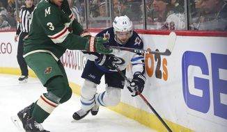 Minnesota Wild center Charlie Coyle (3) defends against Winnipeg Jets defenseman Josh Morrissey (44) in the first period of Game 3 of an NHL first-round hockey playoff series, Sunday, April 15, 2018, in St. Paul, Minn.. The Wild won the game 6-2 but trail the Jets 2-1 in the series. (AP Photo/Andy Clayton-King)