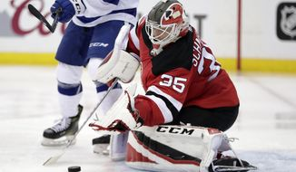 New Jersey Devils goaltender Cory Schneider blocks a shot from the Tampa Bay Lightning during the second period of Game 3 of an NHL first-round hockey playoff series, Monday, April 16, 2018, in Newark, N.J. (AP Photo/Julio Cortez)