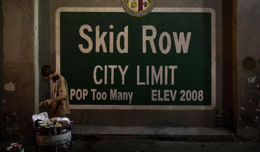 In this Oct. 28, 2017, file photo, a homeless man takes food from a trash can in Los Angeles' Skid Row area, home to the nation's largest concentration of homeless people in Los Angeles. (AP Photo/Jae C. Hong, File)