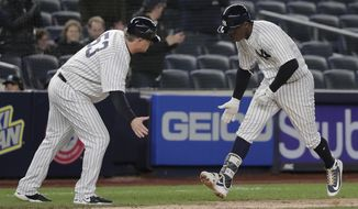 New York Yankees' Didi Gregorius is congratulated by third base coach Phil Nevin (53) after hitting a solo home run against the Miami Marlins during the seventh inning of a baseball game, Monday, April 16, 2018, in New York. (AP Photo/Julie Jacobson)