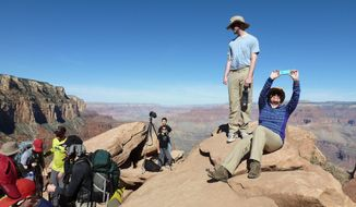 FILE - In this March 16, 2015, file photo, hikers stop and take photos along the Grand Canyon National Park's South Kaibab trail. With diverse landscapes and abundant wildlife, America's national parks are popular travel destinations. To save money on a trip, break out the camping gear and schedule your visit around a fee-free day or during off-peak time. (AP Photo/Anna Johnson, File)