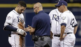 Tampa Bay Rays' Kevin Kiermaier, left, has his hand looked at by team trainer Joe Bench, center, and manager Kevin Cash, right, after injuring it while sliding into second base during the first inning of a baseball game against the Philadelphia Phillies, Sunday, April 15, 2018, in St. Petersburg, Fla. (AP Photo/Chris O'Meara)