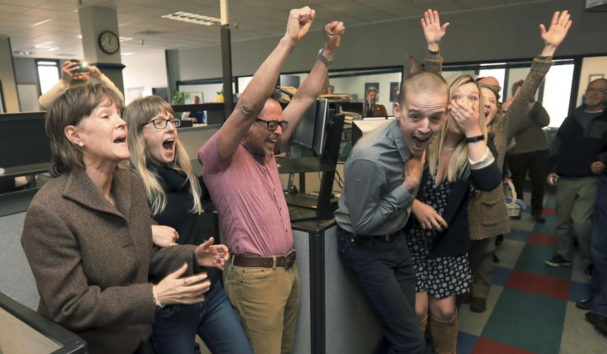 The staff of the Press Democrat including from left, reporters Randi Rossmann Julie Johnson, Martin Espinoza, JD Morris, Christi Warren, Mary Callahan and Director of Photography Chad Surmick celebrate their Pulitzer Prize for breaking news, Monday, April 16, 2018, in Santa Rosa, Calif., for the coverage of the October wildfires. (Kent Porter/The Press Democrat via AP)