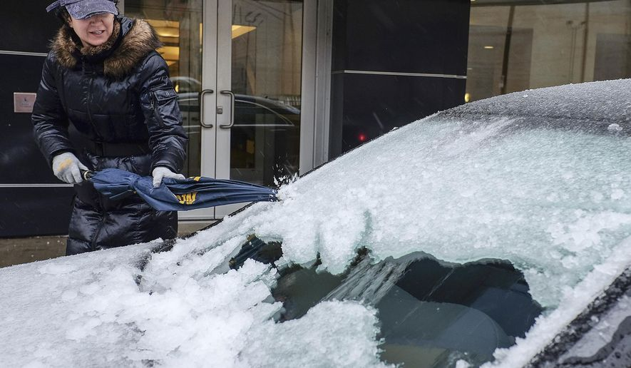 A woman uses an umbrella to chip away at the ice accumulation on her windshield in downtown Lansing, Mich., Sunday, April 15, 2018. Freezing rain that began falling overnight had left roads treacherous and cut power to hundreds of thousands of homes and businesses by midday Sunday in Michigan even as heavy snow was forecast to dump a foot or more of snow on parts of the state's Upper Peninsula by early Monday. (Robert Killips/Lansing State Journal via AP)