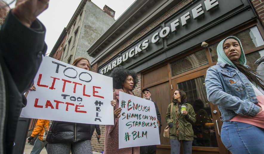 """Protesters gather outside of a  Starbucks in Philadelphia, Sunday, April 15, 2018, where two black men were arrested Thursday after employees called police to say the men were trespassing. The arrest prompted accusations of racism on social media. Starbucks CEO Kevin Johnson posted a lengthy statement Saturday night, calling the situation """"disheartening"""" and that it led to a """"reprehensible"""" outcome.  (Michael Bryant/The Philadelphia Inquirer via AP)"""