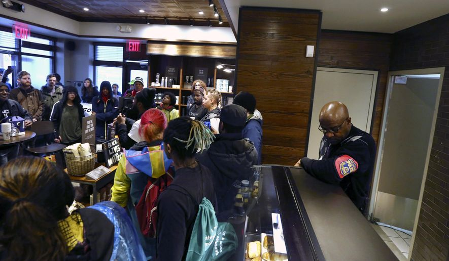 A plain-clothed police officer, right, mans a position behind the counter at the Starbucks that has become the center of protests Monday, April 16, 2018, in Philadelphia. The CEO of Starbucks arrived in Philadelphia hoping to meet with two black men who were arrested when the coffee chain's employees called 911 and said they were trespassing. Meanwhile, protesters took over the shop Monday. (AP Photo/Jacqueline Larma)