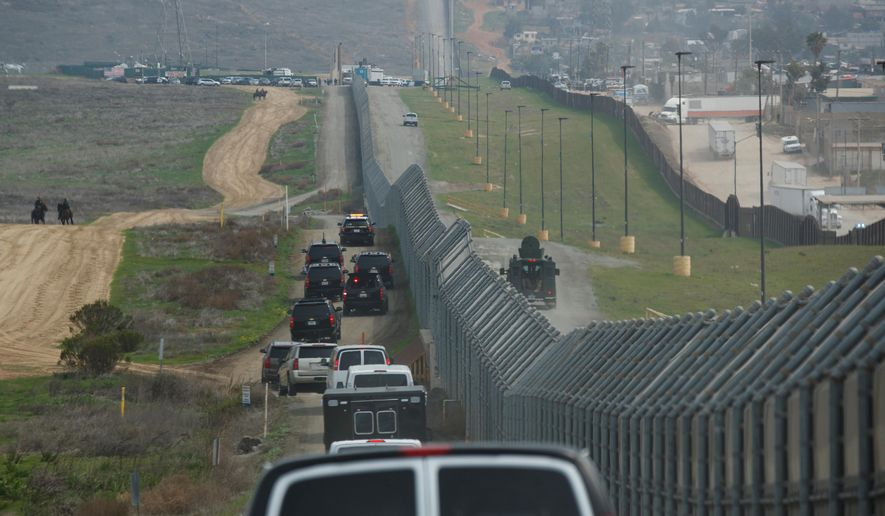 FILE - In this March 13, 2018, file photo, a motorcade carrying President Donald Trump drives along the border in San Diego. California has rejected the federal government's initial plans for National Guard troops to the border because the work is considered too closely tied to immigration enforcement. (AP Photo/Evan Vucci, File)