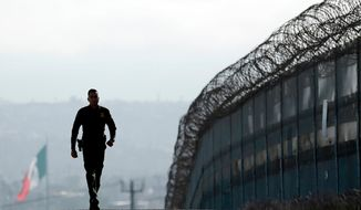 In this June 22, 2016, file photo, Border Patrol agent Eduardo Olmos walks near the secondary fence separating Tijuana, Mexico, background, and San Diego in San Diego. California has rejected the federal government's initial plans for National Guard troops to the border because the work is considered too closely tied to immigration enforcement. (AP Photo/Gregory Bull, File)