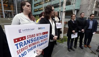 In this March 27, 2018, file photo, plaintiffs Cathrine Schmid, second left, and Conner Callahan, second right, listens with supporters during a news conference in front of a federal courthouse following a hearing in Seattle. A federal judge in Seattle has ordered President Donald Trump not to take any action barring transgender troops from serving in the military, finding that it's unclear whether recent tweaks to his administration's policy are constitutional. In an order Friday, April 13, 2018, U.S. District Judge Marsha Pechman said that because the tweaks were announced just last month, the parties had not had time to argue about whether the policy is unconstitutionally discriminatory or whether the military is entitled to deference. (AP Photo/Elaine Thompson) **FILE**