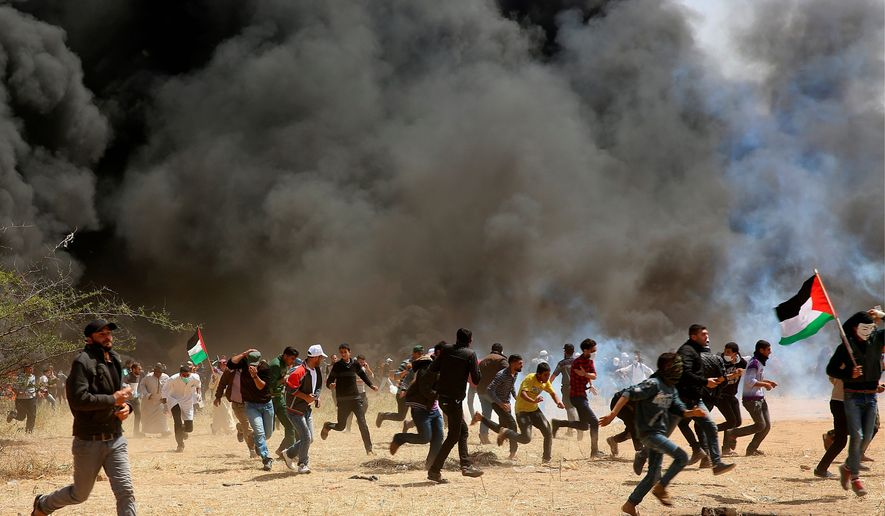 FILE - In this Friday, April 6, 2018 file photo, Palestinian protesters run for cover from teargas fired by Israeli soldiers during clashes with Israeli troops at the Gaza's border with Israel near Khan Younis. The flareup of deadly violence in Gaza is of a new kind, even in the inventive annals of Mideast conflicts: Israeli soldiers shooting at Palestinian demonstrators burning tires and hurling firebombs across what looks like an international border, inflicting casualties while claiming concerns of a mass breach of the barrier. (AP Photo/Adel Hana, File)