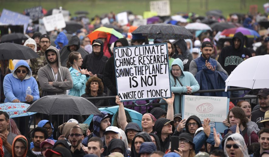 "A person hold up a sign that reads ""Fund Climate Change Research Saving The Planet Is Not A Waste Of Money"" during the March for Science in Washington, Saturday, April 22, 2017. (AP Photo file/Sait Serkan Gurbuz)"