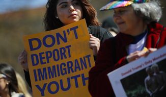 Gabriela Matinez, 19, left, from P.G. County Md., and Liz Milner, from Washington D.C., right, hold a signs as they join immigration advocates from American Civil Liberties Union, Union We Dream, MoveOn and others during the announcement of a new campaign targeted at President Trump's immigration policies, at the Ellipse infront of the White House in Washington, Sunday, March 4, 2018. The U.S. Supreme Court last week refused to consider the Trump administration's unusual request to overrule a judge who kept alive a program that shields young immigrants from deportation. The administration went directly to the nation's highest court after U.S. District Judge William Alsup in San Francisco decided in January that beneficiaries of the Obama-era Deferred Action for Childhood Arrivals program could apply for renewals. (AP Photo/Pablo Martinez Monsivais)