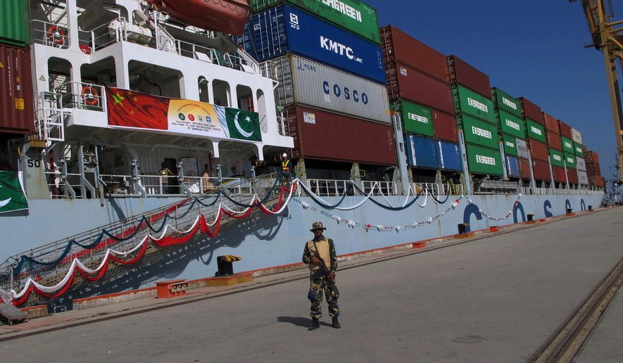 A Pakistani navy member stands guard while a loaded Chinese ship prepares to depart Gwadar Port. A study says the massive Chinese infrastructure program called One Belt One Road that Beijing says is aimed at promoting global trade and economic growth is actually intended to expand the country's political influence and military presence. (Associated Press/File)
