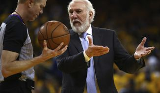 San Antonio Spurs coach Gregg Popovich, right, gestures to a referee during the second half in Game 2 of a first-round NBA basketball playoff series against the Golden State Warriors Monday, April 16, 2018, in Oakland, Calif. (AP Photo/Ben Margot)