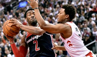 Washington Wizards guard John Wall (2) looks to drive to the net as Toronto Raptors guard Kyle Lowry (7) defends during the second half of Game 2 of an NBA basketball first-round playoff series Tuesday, April 17, 2018, in Toronto. (Nathan Denette/The Canadian Press via AP)